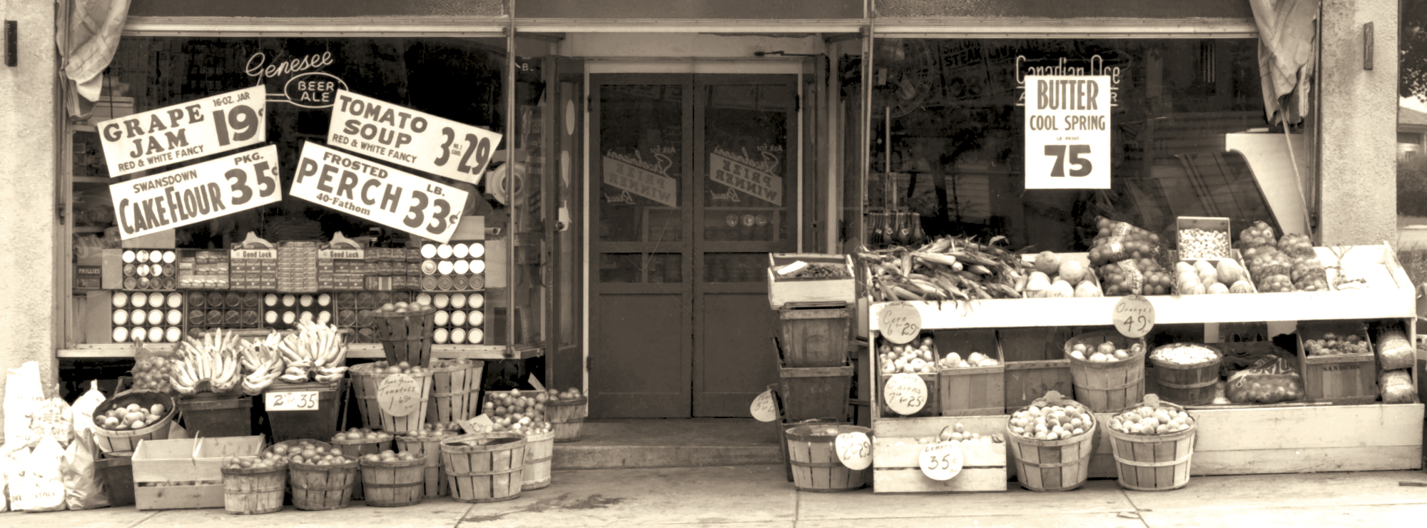 Black and white sepia tone photo showing a produce storefront.
