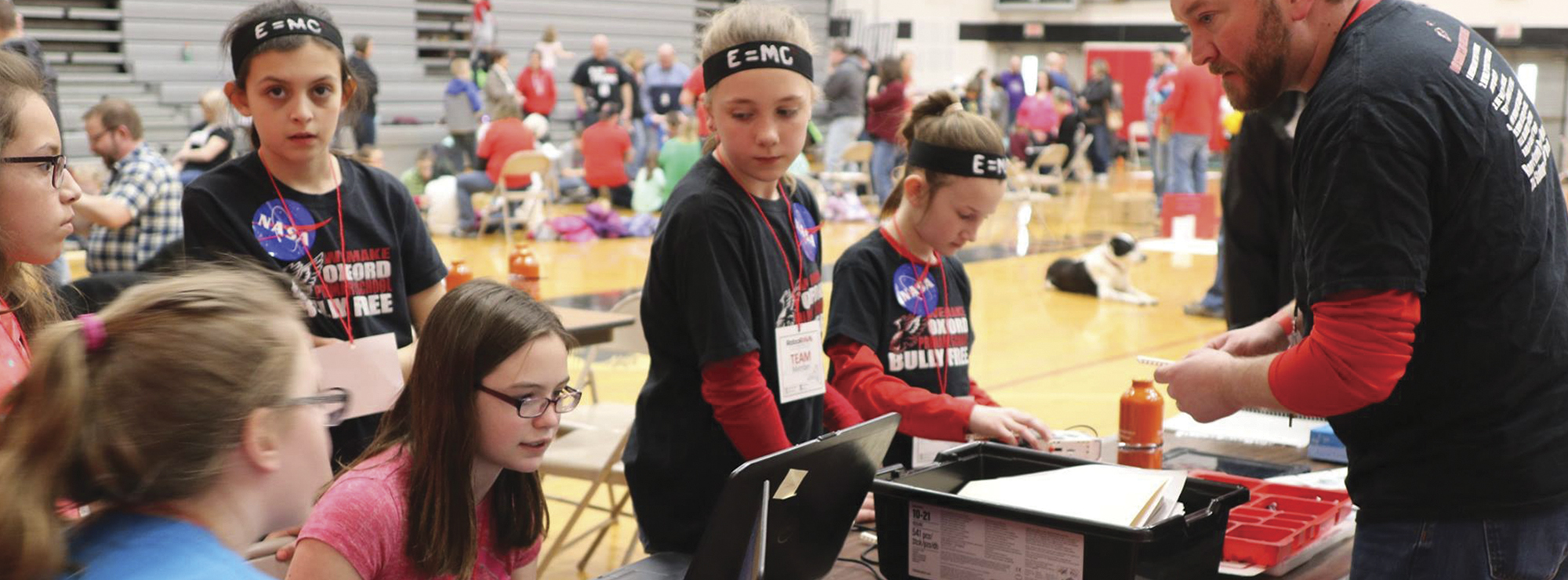 School students in a gymnasium participating in a technology or science fair event.