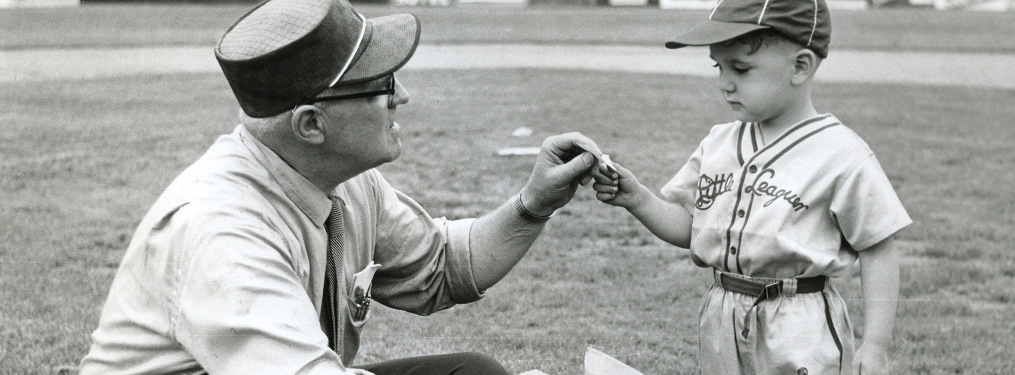 Black and white photo of man with small boy both dressed in period baseball clothing.