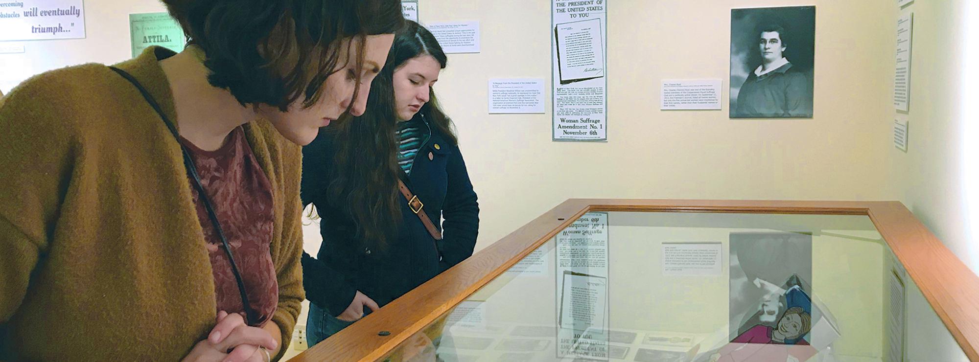 Two young women seen in a museum setting looking at displays.