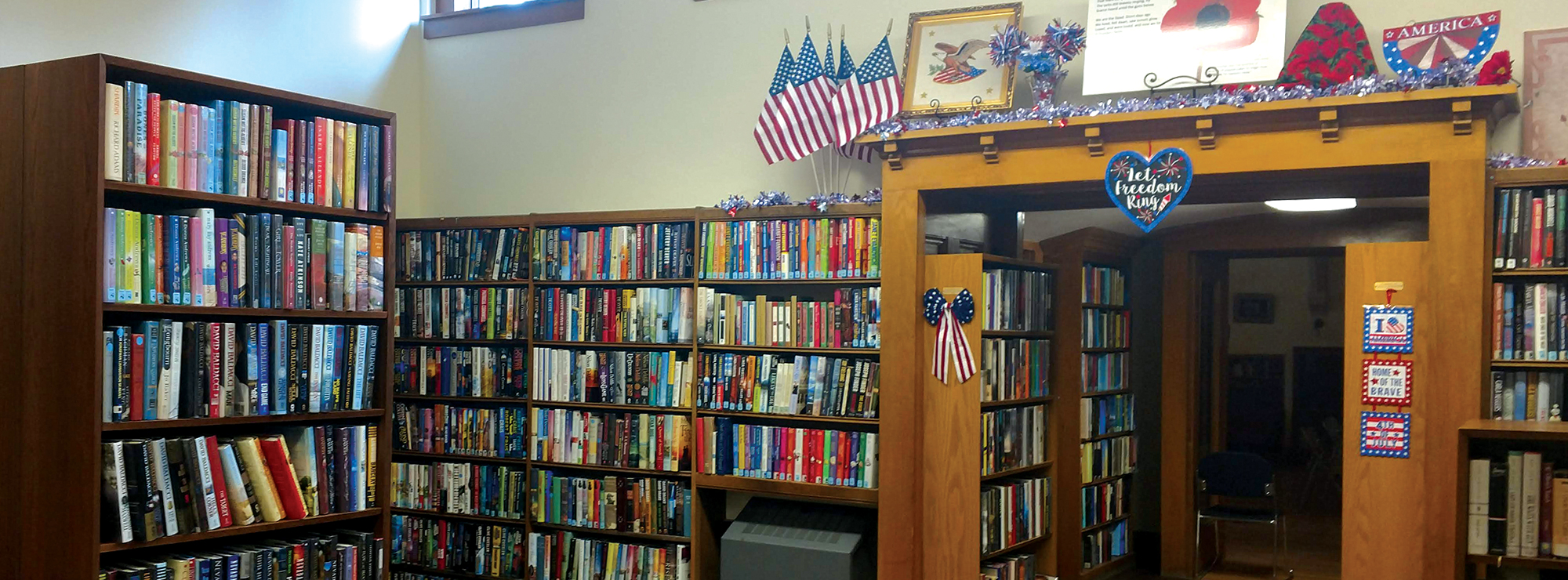 Photo shows library shelves full of books.