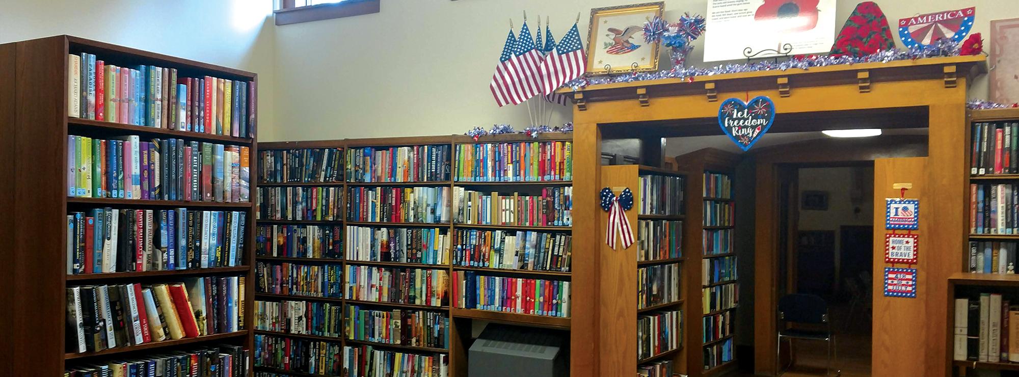 Photo shows library shelves full of books.