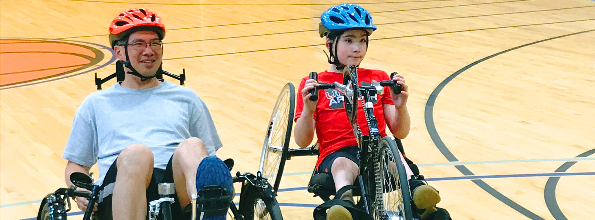 Photo shows two individuals on recumbent bikes.