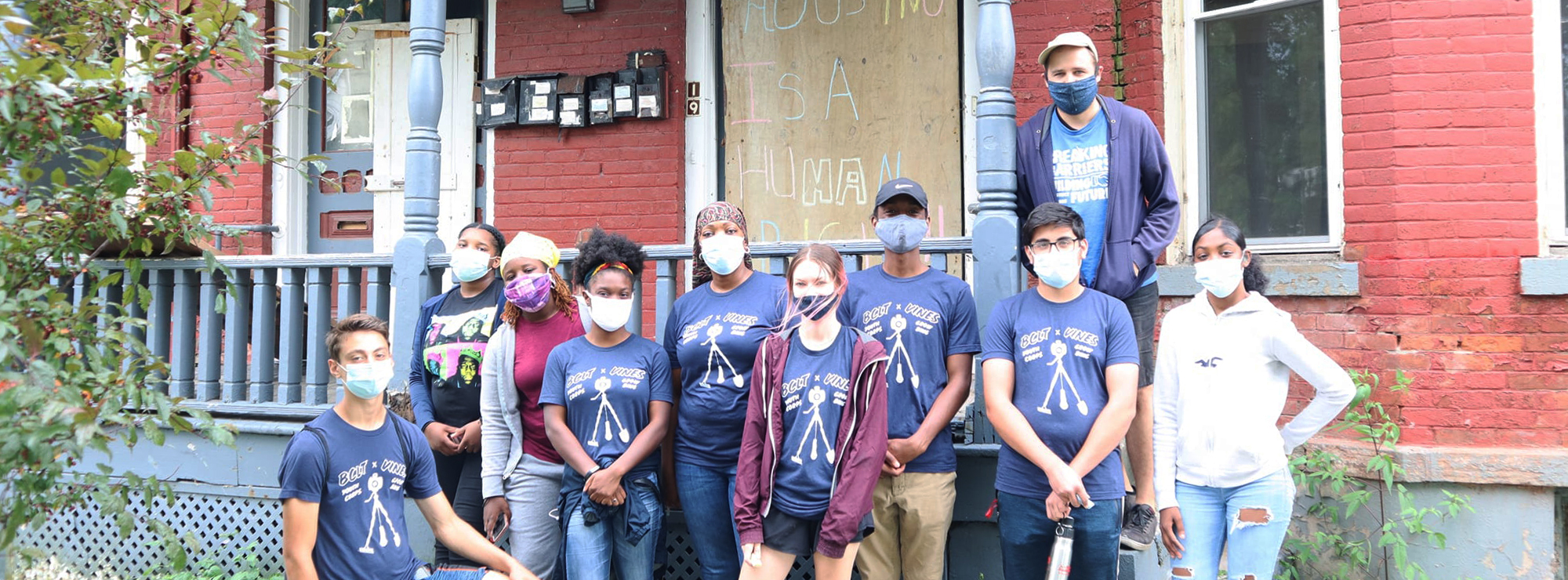 Youth from the Grow Binghamton program shown in front of a dilapidated home.