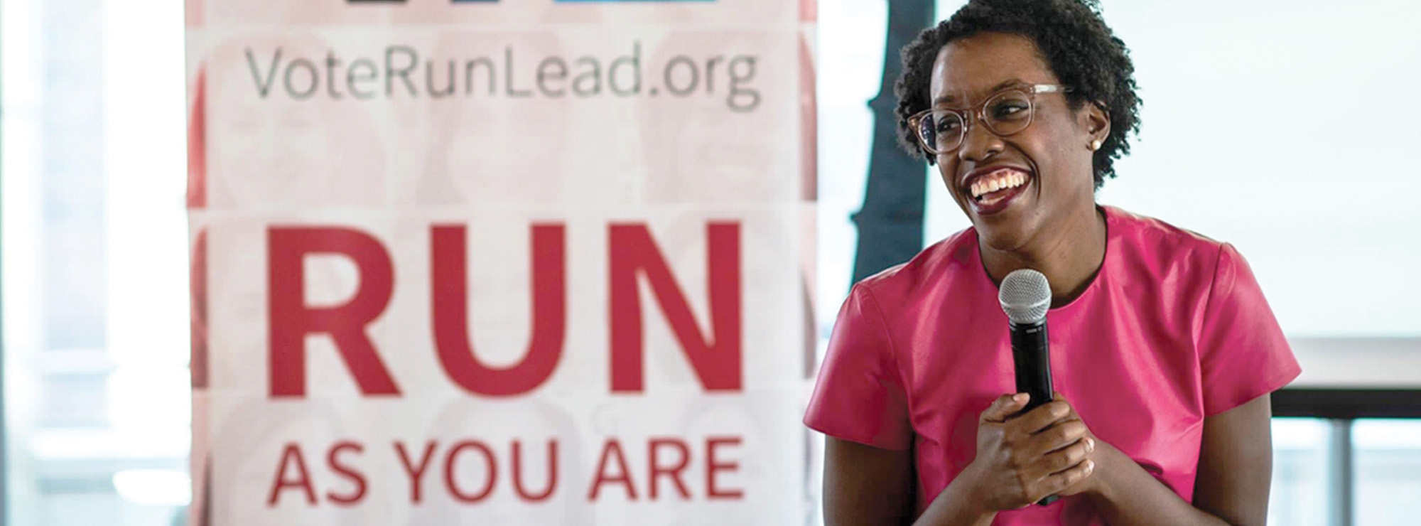 """Photo of a smiling woman holding a microphone and standing in front of a """"Run as you are"""" poster."""